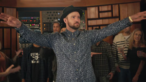 justin timberlake with arms up wearing a fedora and floral print shirt