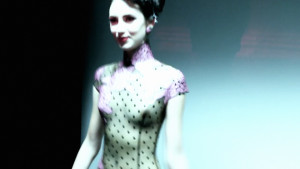 Atsuko Kudo's Lingerie London show, backstage shot of a model in latex corset with breasts exposed