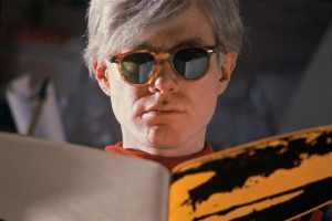 andy warhol wearing glasses and reading a book
