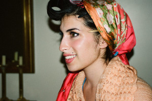woman holding a photograph of amy winehouse in a head wrap and biting her lip