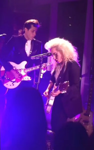 lady gaga and mark ronson playing guitar together on stage in purple light