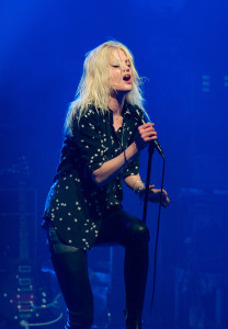 Alison Mosshart of The Kills wearing a star shirt and singing and performing on stage