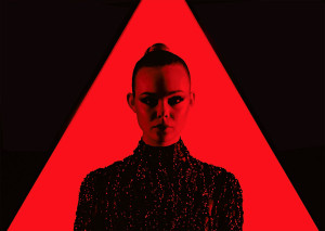 neon demon movie, elle fanning in red triangle and red light wearing a black dress