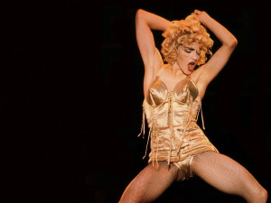 madonna in gold leotard with arms up and legs open