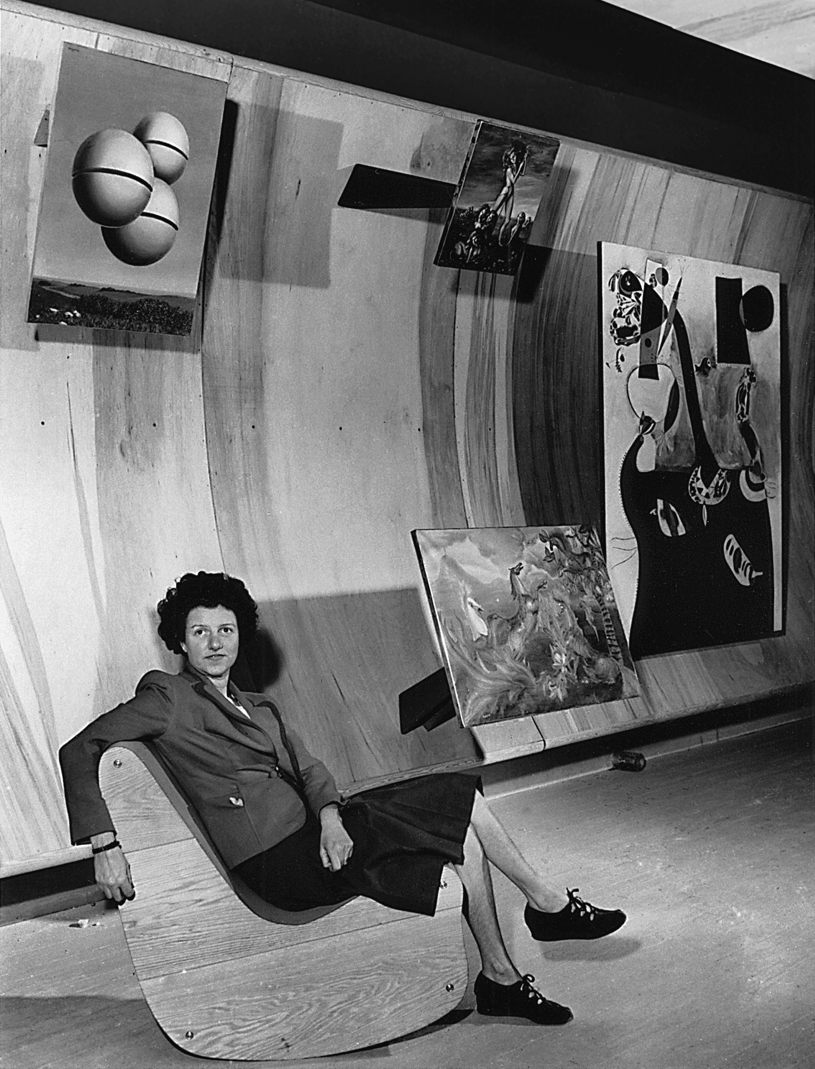 Peggy Guggenheim seated on a Correalist Rocker, Surrealist Gallery, Art of This Century, New York, c. 1942. From left: René Magritte, Voice of Space (La voix des airs, 1931); Leonor Fini, The Shepherdess of the Sphinxes (1941); Leonora Carrington, The Horses of Lord Candlestick (1938); and Joan Mirò, Dutch Interior II (1928). © AP Photos courtesy Solomon R. Guggenheim Foundation, New York, 2017.